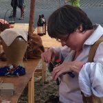 Edith beim Basteln - auch wenn die Lochzange nicht historisch ist, der fertige Besteckbeutel wird es sein :)